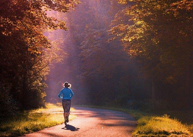 Vrouw loopt hard op een geasfalteerde weg in het bos